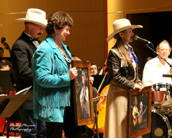 Kathi Mustrave and Belinda Gail receive portriats of the late Curly Mustrave